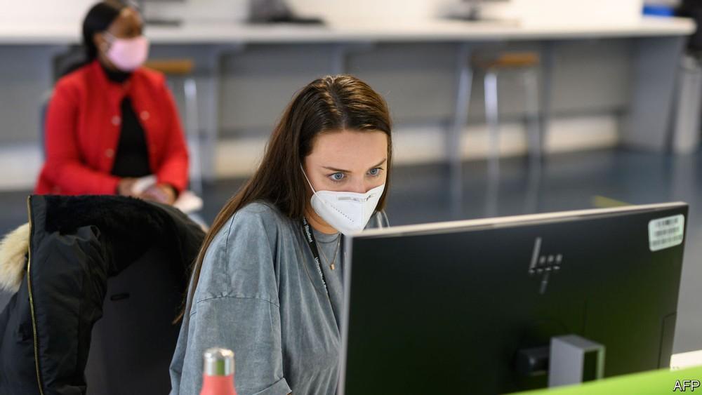 woman looking at monitor wearing mask serious hp-monitor
